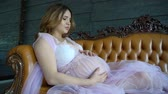 girlish : Beautiful charming pregnant woman with brown hair sitting on the couch in a lilac vintage dress Stock Footage