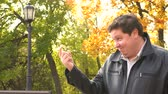 provérbio : Smiling fat man showing come closer gesture with finger in autumn park Stock Footage