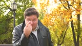ухмыляясь : Smiling fat man showing come closer gesture with finger in autumn park Стоковые видеозаписи