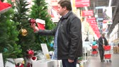 gastos : Man preparing for Christmas and New Year holidays. Fat male chooses or buying decorations in hypermarket Vídeos