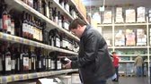 Young attractive fat man is choosing the good bottle of wine in the supermarket