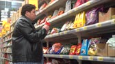 Young fat man selecting snacks in the sweets section at the supermarket