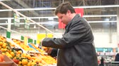 Fat man picking out fruit, oranges in supermarket