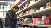 Young fat man picking out sweet candy, dessert in supermarket in high quality