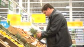 Young fat man picking out fruit, pineapple in supermarket