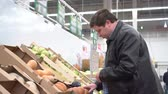 Young fat man picking out pumpkin vegetables in supermarket, preparation for halloween or vegetable diet Wideo