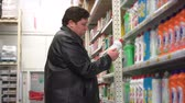 Young fat man chooses household chemicals in the supermarket. Wideo