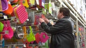 Young fat man chooses kitchen accessories in the supermarket