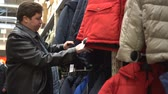 Man chooses a winter jacket in the store