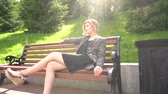 Camera moves away from beautiful fashion young woman sitting on bench under sunlight in summer park