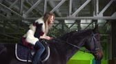 riding arena : Animal, horse riding concept. Young woman sitting on horse and stroking its fringe