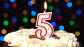 five : Number 5 on top of cake - five birthday candle burning - blow out at the end. Color blurred background Stock Footage