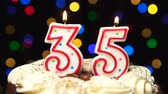 trinta anos : Number 35 on top of cake - thirty five birthday candle burning - blow out at the end. Color blurred background