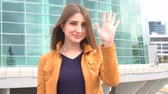 hélio : Beautiful young woman, greeting, waving hand outdoor in the city.