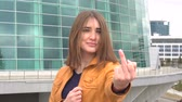 grosseiro : Very beautiful girl makes obscene hand gesture by showing middle finger in the city outdoor.
