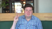 тридцать : A handsome, fat man with big body shows victory sign in the cafe or restaurant