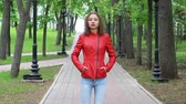 bright clothes : Beautiful girl wearing red leather jacket in autumn park