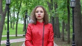 bright clothes : Young woman wearing a red jacket looking at camera in a green park