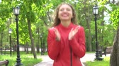 görme : Successful young woman in red leather jacket applauding, multiple action Stok Video