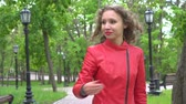aliciamento : young woman in red jacket inviting someone to come in park. Stock Footage