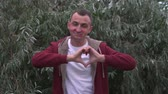 cuore sagoma : Young man with face full of lipstick marks of kisses is making heart shape with hands