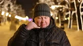 kontakt : Portrait of handsome man making a gesture call me with his fingers outdoors during cold winter night Wideo
