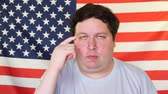 demokrasi : Young man thinking about something on the background of an USA flag Stok Video