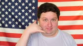 call me : Young man making call me gesture on the background of an USA flag Stock Footage