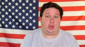 törülköző : Fat man, wiping the sweat with a handkerchief on the background of an USA flag Stock mozgókép