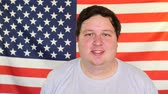 いちゃつく : Young fat man winking on the background of an USA flag