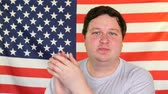 aplauso : Young fat man clapping on the background of an USA flag