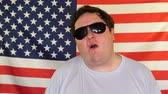 chicle : Young man in sunglasses chewing bubble gum on the background of an USA flag