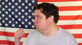 pozvat : Side view of young fat man who invites someone on the background of an USA flag