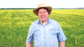 nevetés : Portrait of happy farmer who stands and laughs in the field on a sunny day