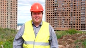 munkatársai : Male builder foreman or architect working on construction building site standing while laughing and smiling to camera