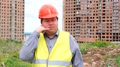 call me : Male builder foreman, worker or architect on construction building site showing call me gesture
