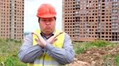 munkatársai : Male builder foreman, worker or architect on construction building site showing hand gesture stopping crossing his arms