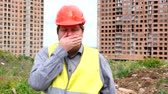 munkatársai : Young handsome builder man covering mouth on construction site