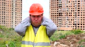 munkatársai : young handsome builder is afraid (man covers his ears with hands) - construction site