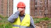 personnel : Builder is afraid (man covers his eyes with hands) - construction site