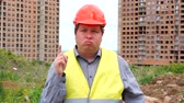 munkatársai : Male builder foreman, worker or architect on construction building site does not agree waving his finger