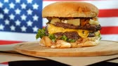 susam : Grilled American beef burger with lettuce, cheese, onion served on pieces of brown paper rotating on a wooden counter. Stok Video