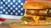 ajonjoli : Grilled American beef burger with lettuce, cheese, onion served on pieces of brown paper rotating on a wooden counter. Archivo de Video