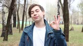 bem : Portrait of handsome caucasian happy young man showing ok sign in the park