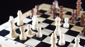 rycerz : Slow tracking shot behind chess pieces on wooden chess board