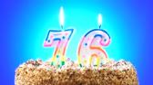 torta compleanno : Birthday cake with a burning birthday candle. Number 76. Background changes color