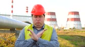 petrochemical : Worker showing stop sign, rejecting gesture, disagree sign, crossing hands, standing in front of a power station