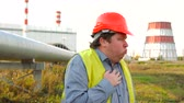 refinaria : Worker, engineer, or electrician looking directly at the camera coughing standing in front of a power station