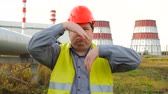 petrochemical : Worker, engineer, or electrician looking directly at the camera funny dancing in front of a power station