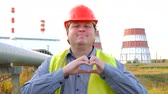 cuore sagoma : Happy worker, engineer, or electrician looking at the camera and showing love gesture in front of a power station Filmati Stock